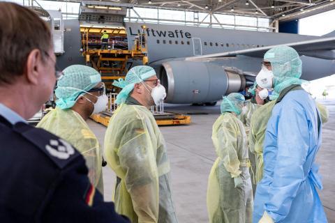 """Personal médico con equipos de protección individual que abandonan el Airbus A310 """"Medevac"""" junto con pacientes con coronavirus después de aterrizar en Colonia, Alemania, el 28 de marzo."""