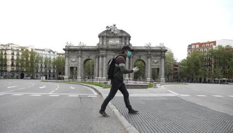 Un hombre cruza la calle con una mascarilla puesta ante la Puerta de Alcalá de Madrid