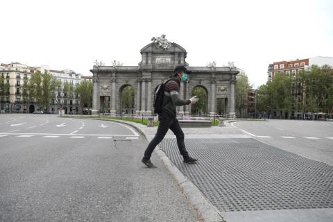 Un hombre pasea por delante de la Puerta de Alcalá en medio del confinamiento por el coronavirus