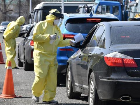Personal sanitario dando indicaciones a un grupo de conductores en Goyang, Corea del Sur, el 29 de febrero.
