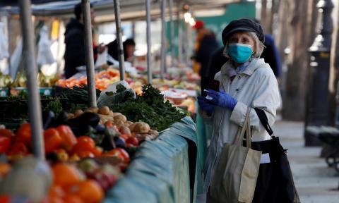 Una mujer compra con mascarilla y guantes en un mercado de París