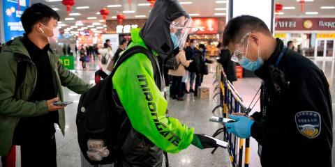Un pasajero muestra un código QR verde en su teléfono que indica su estado de salud a la seguridad al llegar a la estación de tren de Wenzhou el 28 de febrero de 2020.