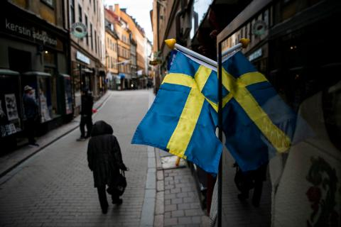 People walk in the main street of the old town in Stockholm, Sweden, on March 25, 2020, as the world fights the coronavirus.