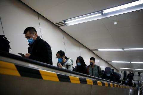 Pasajeros del metro en una escalera mecánica llevan mascarillas de protección.