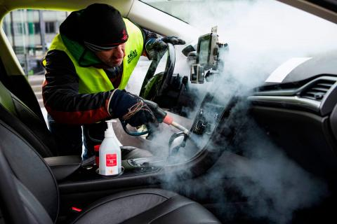 A person cleans and disinfects a taxi car in Stockholm, Sweden, on March 24, 2020, to prevent the spread of the coronavirus.