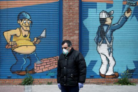 Una persona pasea con mascarilla por la calle en medio del confinamiento por el coronavirus