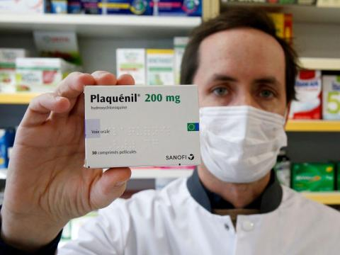 A pharmacy worker with a box of hydroxychloroquine on March 25.