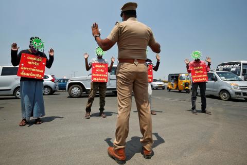 Un policía de Chennai (India) obliga a 4 personas que se han saltado el confinamiento a llevar una careta que representa al coronavirus y un cartel que les identifica como infractores