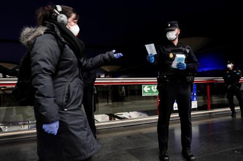 Un policía reparte mascarillas en una estación de Metro en Madrid.
