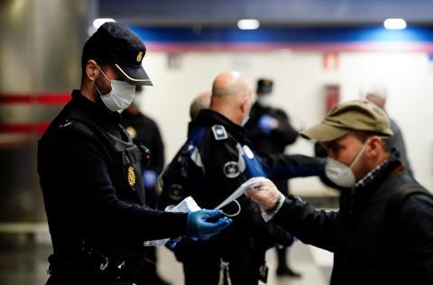 Un policía reparte mascarillas higiénicas en una estación de Metro de Madrid.