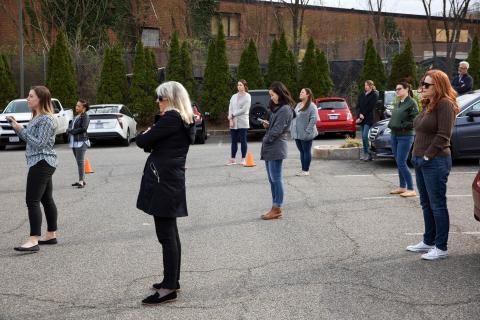 """El personal de """"Food and Friends"""", un servicio de distribución de alimentos para personas con enfermedades crónicas, practican el distanciamiento social mientras escuchan a la alcaldesa del Distrito de Columbia, Muriel Bowser."""