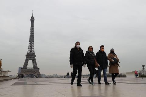Turistas con mascarillas protectoras frente a la Torre Eiffel de París, el 17 de marzo de 2020, unas horas antes de que entre en vigor el confinamiento.