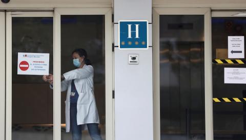 Una trabajadora sanitaria coloca un cartel en un hotel medicalizado en Madrid