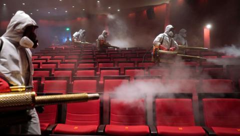 Trabajadores del Ministerio de Sanidad chino desinfectan un cine en Wuhan