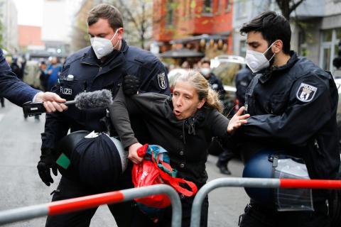 Una mujer habla con un reportero mientras es detenida por la policía durante una manifestación contra las medidas de cierre en Berlín, el 25 de abril de 2020.