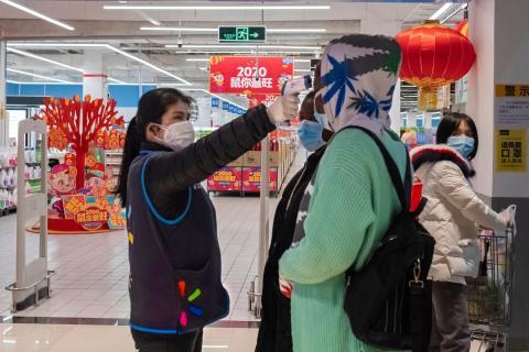 Una trabajadora toma la temperatura de un cliente en Walmart, en Wuhan, China.