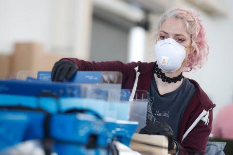 Una trabajadora lleva protección especial durante la fabricación de protección para sanitarios.