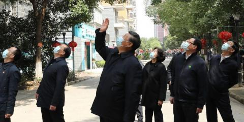 Xi waves to quarantined residents in Wuhan on March 10.
