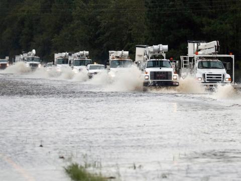 Un convoy de camiones utilitarios que se dirigen al este para ayudar con los daños causados por la tormenta tropical Florence se abre paso a través de un tramo de autopista.