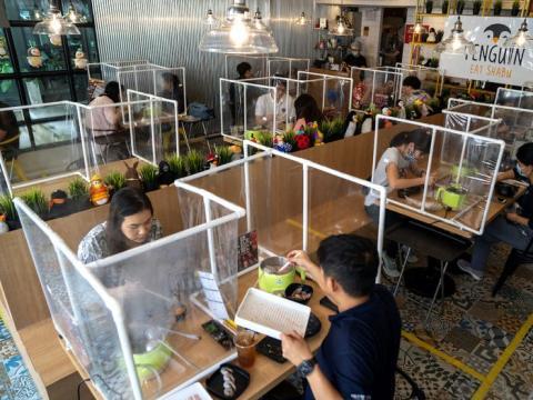Una barrera de plástico permite a los clientes disfrutar de su estofado en un restaurante.