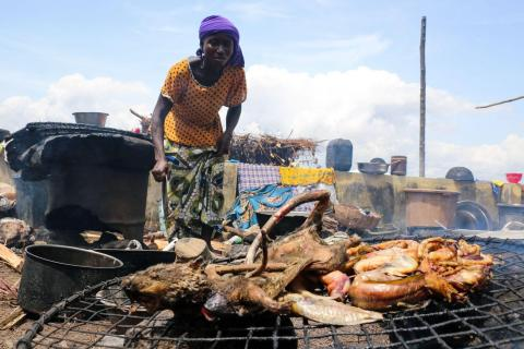 A woman displaced by the recent wave of floods in Konto Karfi, prepares to roast bushmeat at an outdoor facility of an Internally displaced people (IDPs) camp in Otokiti, Kogi State, on September 19, 2018