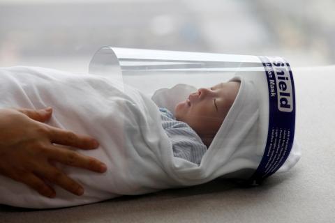 Un bebé con una pantalla protectora para protegerse del coronavirus en un hospital de Vietnam