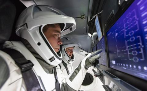 Los astronautas de la NASA Bob Behnken (primer plano) y Doug Hurley (fondo) entrenan dentro de la nave espacial Crew Dragon de SpaceX.