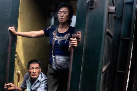 Gente relajándose en la puerta de un vagón de tren (Corea del Norte, agosto de 2015).