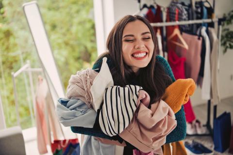 Chica joven con ropa en la mano