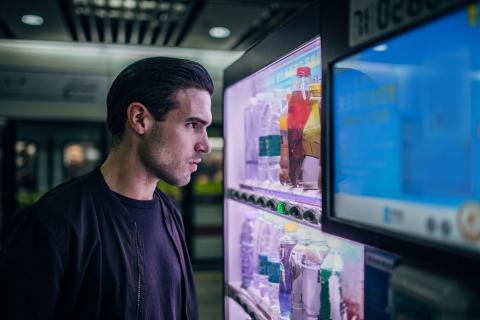 Un chico frente a una máquina expendedora.