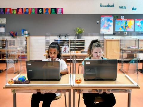 Alumnos sentados detrás de tableros de plexiglás asisten a clase en una escuela primaria en Den Bosch, Países Bajos, 8 de mayo de 2020.