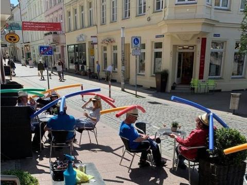 Sentados en la terraza, los clientes de Café & Konditorei Rothe utilizan sombreros hechos con churros de piscina.