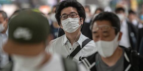 Gente desplazándose con mascarilla en Japón.