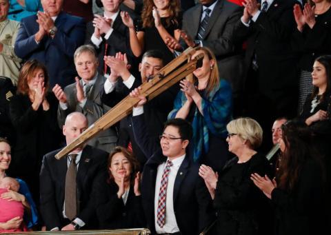 Ji sostiene sus muletas durante el discurso de Trump.