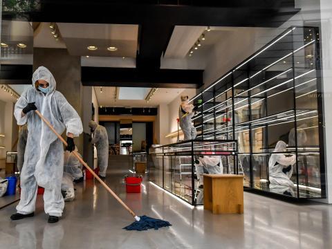 Trabajadores con trajes de protección desinfectan una tienda en la calle comercial de moda Monte Napoleone, en Milán, Italia, el 27 de abril de 2020.