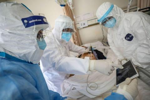 A doctor examines a patient who is infected by the coronavirus at a hospital in Wuhan, in China's Hubei province.
