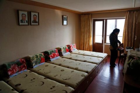 Un empleado se encuentra dentro de una habitación en un dormitorio provisto para trabajadores de fábricas textiles.