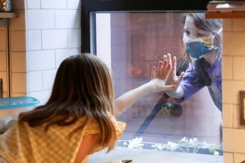 Dos amigas se saludan a través de una ventana en medio de la cuarentena por la pandemia del coronavirus en Nueva York