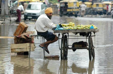 An Indian fruit vendor, Bhupinder Sethi sits on a flooded street as he waits for customers near the bus stand in Punjab.