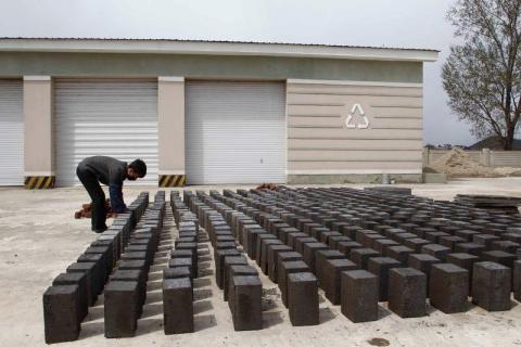 Un trabajador coloca bloques hechos de cenizas de carbón en el suelo mientras en Pyongyang, el martes 21 de abril de 2020.