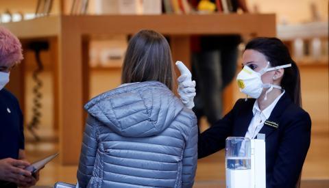 Una empleada de la Apple Store de Zurich (Suiza) mide la temperatura de una clienta