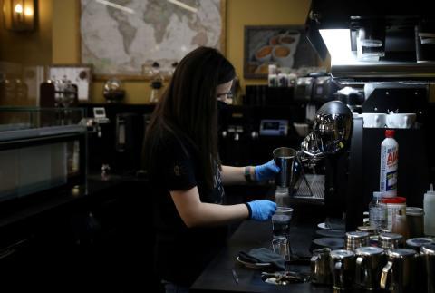 Una empleada de un restaurante de Atenas, Grecia, mientras trabaja con guantes y mascarilla por el coronavirus.