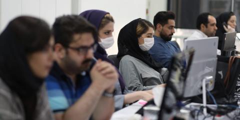 Empleados de una firma de agentes de bolsa vigilan los precios de las acciones en Teherán, Irán, el 12 de mayo de 2020.