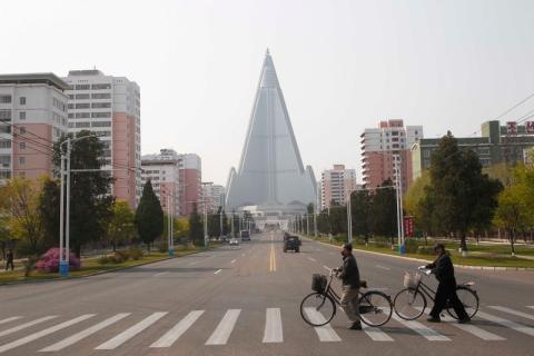 Personas con máscaras cruzan una calle frente al Hotel Ryugyong en Pyongyang, Corea del Norte, el martes 28 de abril de 2020.