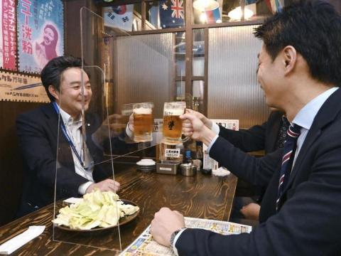 Estos dos hombres en el restaurante brindan, pero no se oye el tintineo de sus vasos.
