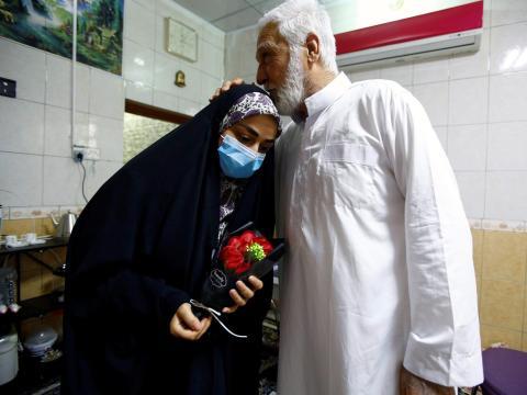 Farah Al-Awadi, una mujer iraquí de 28 años se recuperó de COVID-19, usa una mascarilla mientras su padre la besa en su casa en Najaf, Iraq, el 1 de abril de 2020.