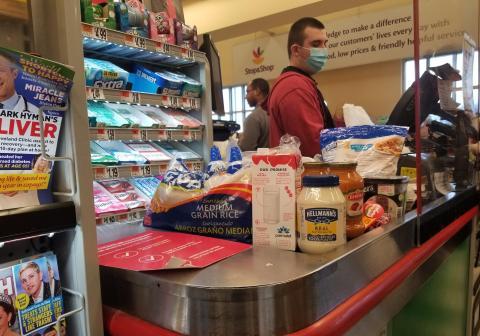 Un cajero con mascarilla ordena las compras detrás de una barrea de plexiglás en Queens, Nueva York.