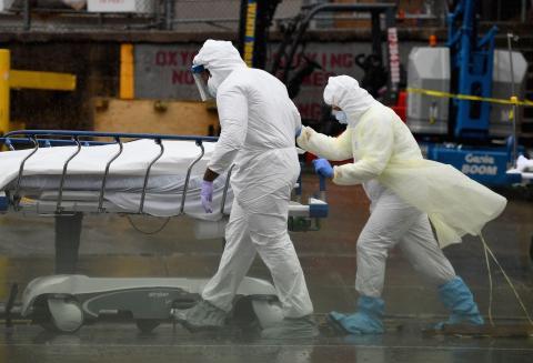 Personal médico traslada a un paciente fallecido a un camión frigorífico que sirve como morgue improvisada en el Centro Hospitalario de Brooklyn el 9 de abril de 2020, en la ciudad de Nueva York.
