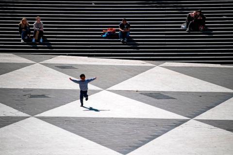 Un niño juega en una plaza.