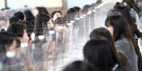 High school students eat lunch at a cafeteria with plastic screens on the table as schools reopen in Daejeon, South Korea, May 20, 2020.